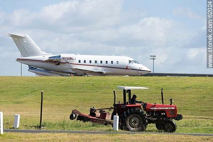 Private jets at the airport in Punta del Este and a tractor mowing the lawn - Photos of Laguna del Sauce, URUGUAY. Image #62024